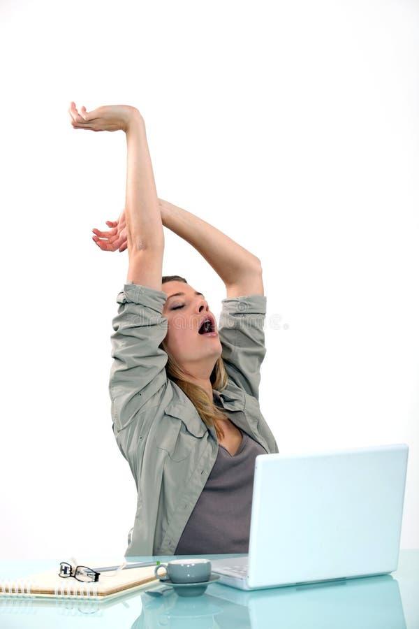 Frau, die am Schreibtisch gähnt stockbild