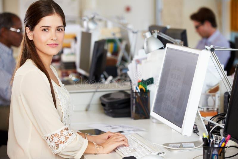 Frau, die am Schreibtisch im besetzten kreativen Büro arbeitet lizenzfreie stockfotografie
