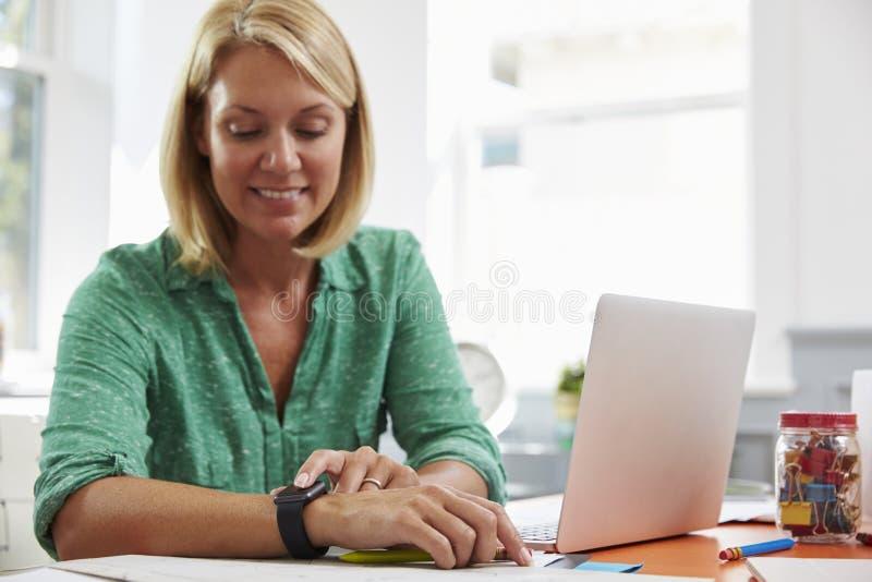 Frau, die am Schreibtisch im Innenministerium betrachtet intelligente Uhr sitzt lizenzfreies stockbild