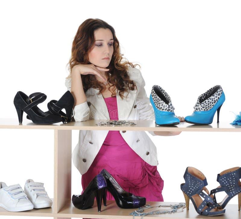 Frau, die Schuhe an einem Speicher wählt stockfoto