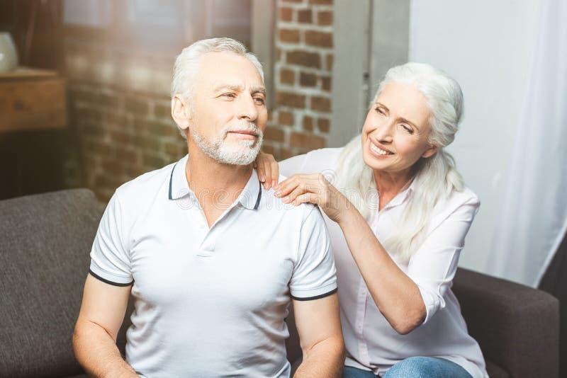 Frau, die Schultermassage für Ehemann macht stockbild