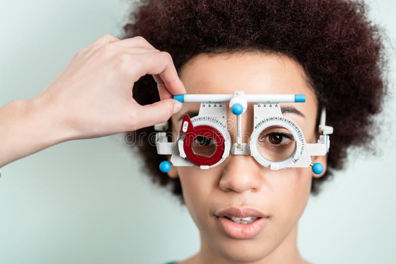 Frau, die Sehvermögentest mit phoropter für neue Gläser hat lizenzfreie stockbilder