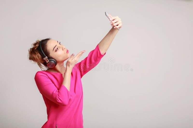 Frau, die selfie auf Smartphone macht und Luftkuß sendet stockfotos