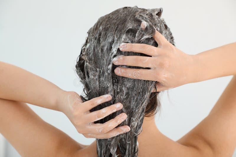 Frau, die Shampoo auf ihr Haar anwendet stockbild