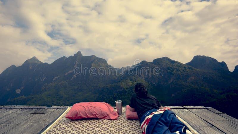 Frau, die sich auf hölzernem Balkon und Berg im Hintergrund hinlegt stockbild