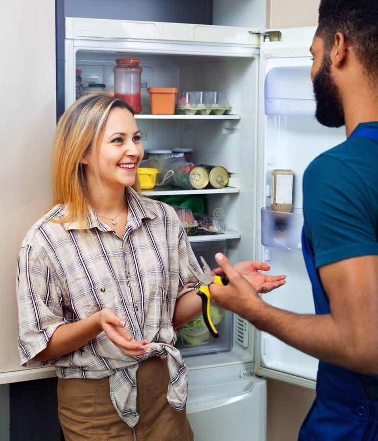 Frau, die sich beschwert, um Heimwerker auf Problemen mit Kühlschrank zu schwärzen lizenzfreie stockfotografie