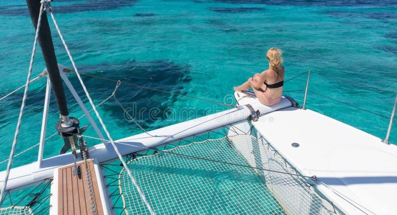 Frau, die sich nahe auf einer Sommersegelnkreuzfahrt, Sitzen auf einem Luxuskatamaran Türkisblaulagune des Bildes in der perfekte stockbilder