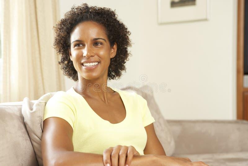 Frau, die sich zu Hause auf Sofa entspannt stockfotografie