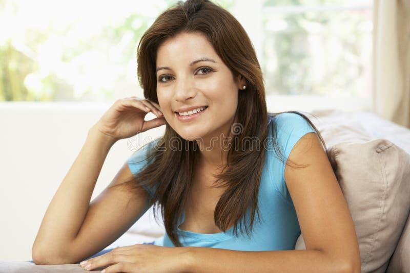 Frau, die sich zu Hause auf Sofa entspannt lizenzfreie stockfotos