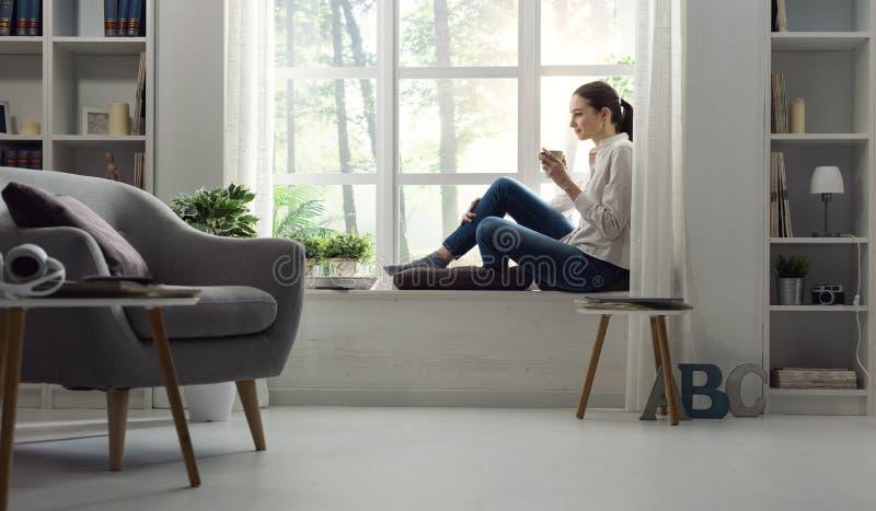 Frau, die sich zu Hause entspannt und Kaffee trinkt lizenzfreies stockbild