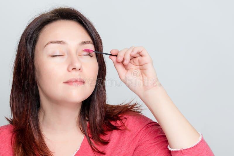 Frau, die sie tut zu bilden, Peitschen, bürstende Wimpern unter Verwendung des Bürstenwerkzeugs vorbereitend Kosmetisches Verfahr stockbilder