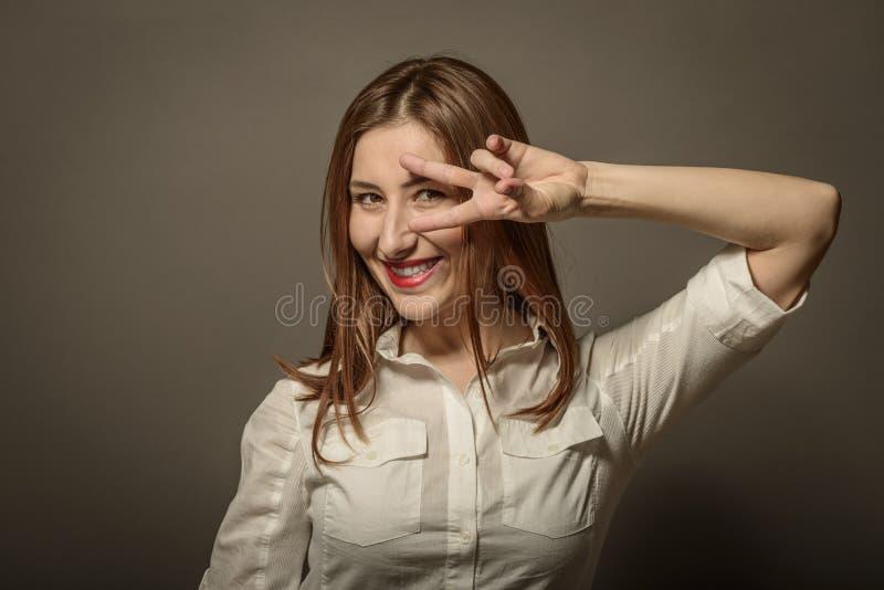 Frau, die Siegzeichen zeigt lizenzfreie stockfotografie