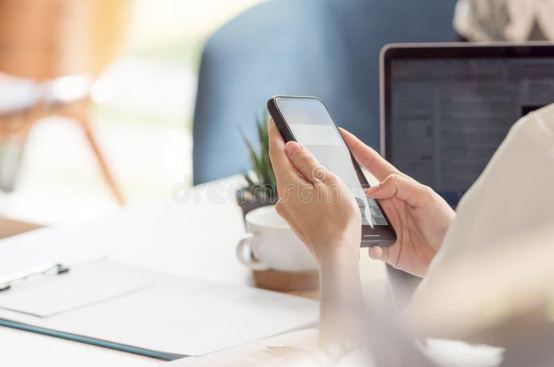 Frau, die Smartphone beim Arbeiten am Schreibtisch im Büro verwendet stockfotografie