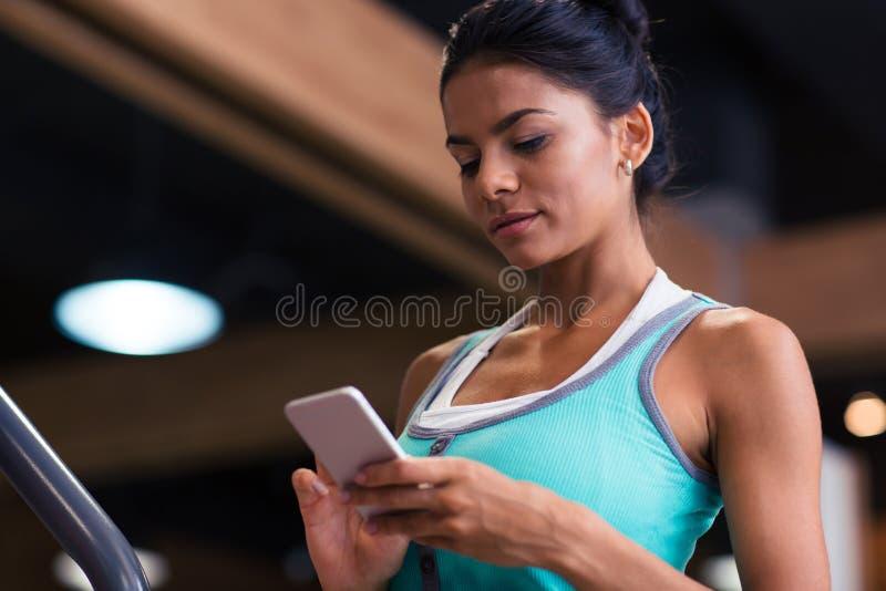 Frau, die Smartphone in der Eignungsturnhalle verwendet stockfotos