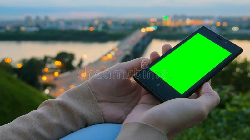Frau, die Smartphone mit gr?nem Schirm betrachtet lizenzfreie stockfotos