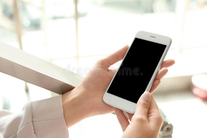 Frau, die Smartphone mit leerem Bildschirm hält lizenzfreie stockfotos