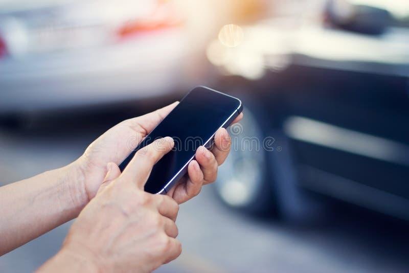 Frau, die Smartphone am Straßenrand nach Verkehrsunfall verwendet stockbild