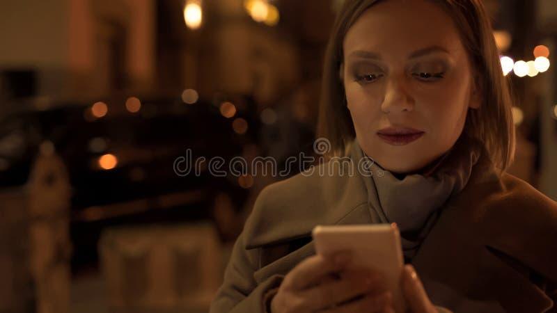 Frau, die Smartphoneschirm-Überfahrtstraße, Risiko des Unfalles, Sucht betrachtet lizenzfreies stockfoto