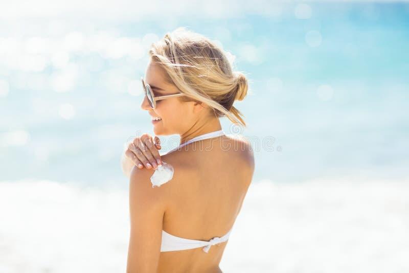 Frau, die Sonnencreme auf ihrer Schulter aufträgt stockfotografie