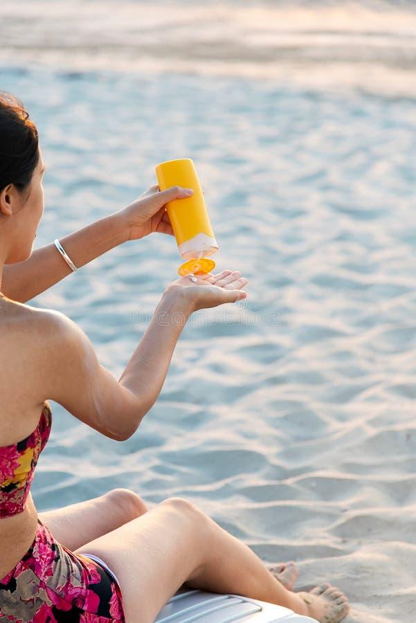 Frau, die Sonnenlotion auf dem Strand verwendet stockfoto