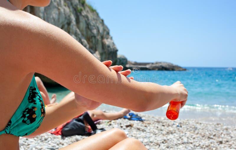 Frau, die Sonnenschutzmittelöl an ihrem Körper aufträgt lizenzfreie stockfotografie