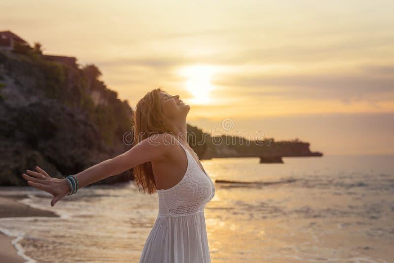 Frau, die Sonnenuntergang auf dem Strand genießt lizenzfreie stockfotos