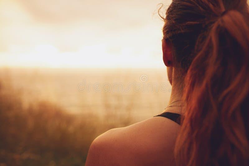 Frau, die Sonnenuntergang betrachtet stockfotografie