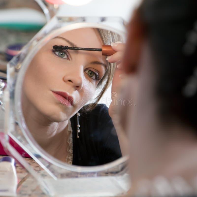 Frau, die Spiegel betrachtet stockfoto