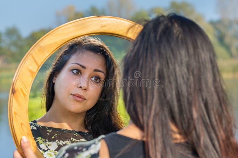 Frau, die Spiegel in der Natur betrachtet stockfotos