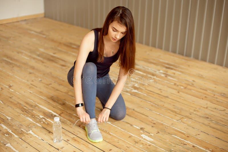 Frau, die Spitzee auf den Sportschuhen sich vorbereiten, ihr Training in der Turnhalle zu beginnen bindet lizenzfreies stockbild