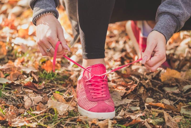 Frau, die Spitzee von Laufschuhen vor der Ausbildung bindet stockfotos
