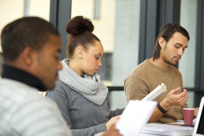 Frau, die stark für Prüfungen in der Bibliothek studiert lizenzfreie stockbilder