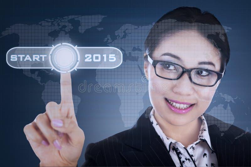 Frau, die Startknopf drückt lizenzfreies stockbild