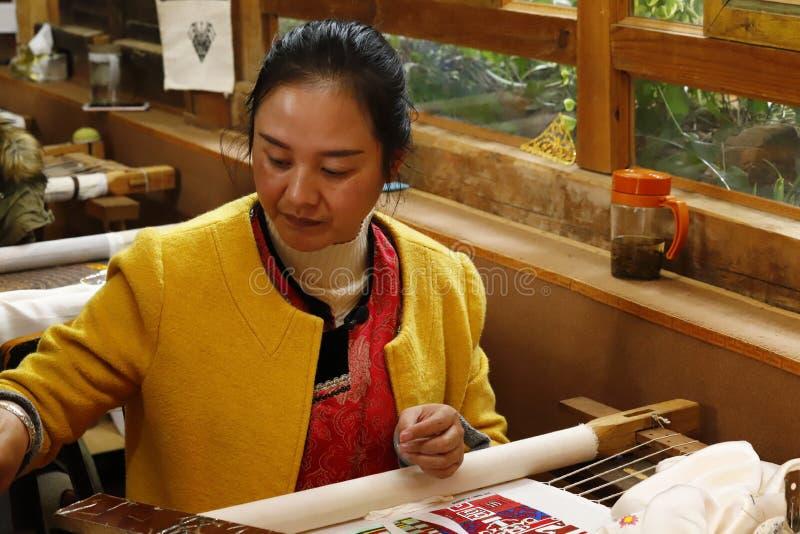 Frau, die an Stickerei im Dorf von Baisha, Lijiang, Yunnan, China arbeitet lizenzfreie stockfotos