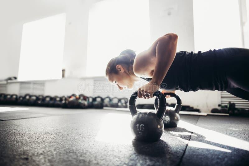 Frau, die StoßUPS-Übungen auf kettlebells tut Geeignetes Training des Kreuzes lizenzfreie stockfotografie