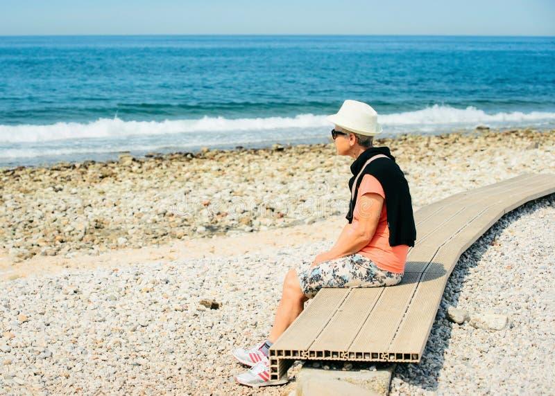 Frau, die am Strand in Izola sitzt lizenzfreie stockfotos