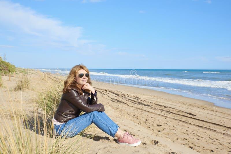 Frau, die am Strand sich entspannt stockfotografie