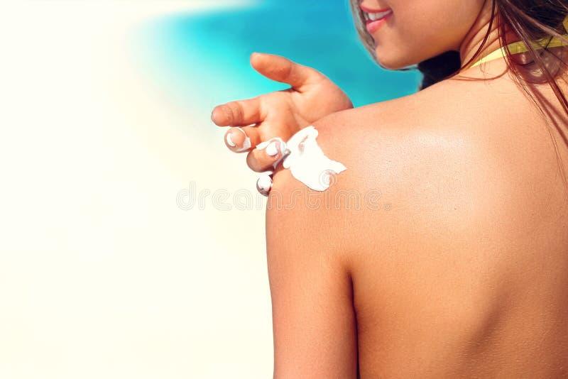 Frau, die sunblock Lotion auf Schulter bevor dem Br?unen w?hrend der Sommerferien auf Strandferienort setzt lizenzfreies stockbild