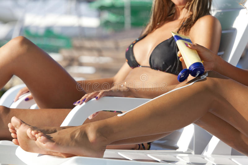 Frau, die Suntanlotion anwendet stockfotos