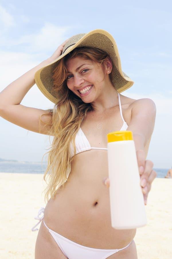 Frau, die Suntanlotion am Strand anwendet lizenzfreies stockfoto