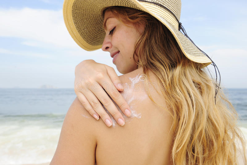 Frau, die Suntanlotion am Strand anwendet stockfotografie