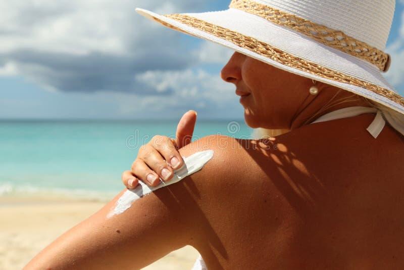 Frau, die Suntanlotion am Strand anwendet lizenzfreie stockbilder