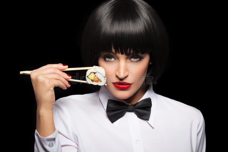 Frau, die Sushi durch Essstäbchenporträt hält stockfoto