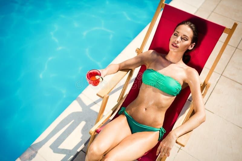 Frau, die am Swimmingpool ein Sonnenbad nimmt stockbild