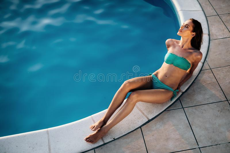 Frau, die am Swimmingpool ein Sonnenbad nimmt stockfotos