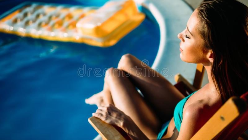 Frau, die am Swimmingpool ein Sonnenbad nimmt stockfoto