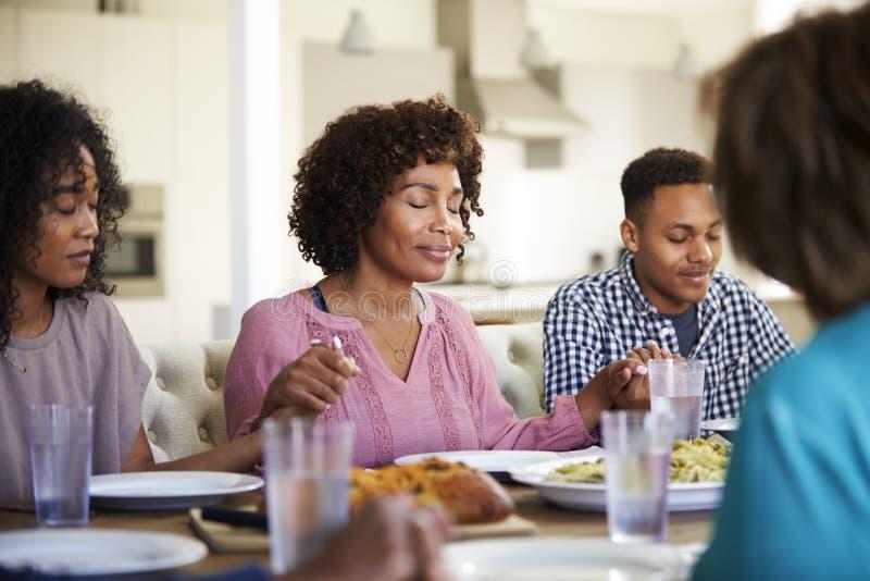 Frau, die am Tabellenhändchenhalten mit ihren jungen erwachsenen Kindern sagen Anmut vor Abendessen sitzt lizenzfreies stockbild