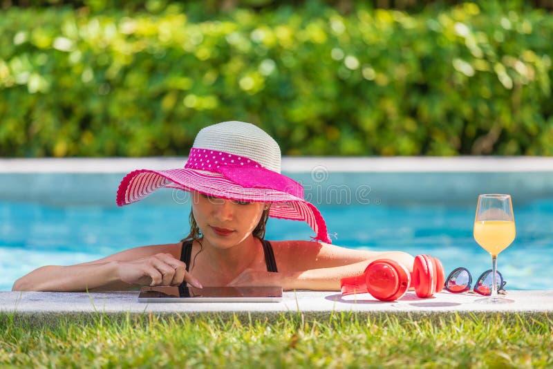 Frau, die Tablet-Computer im Pool verwendet stockfoto