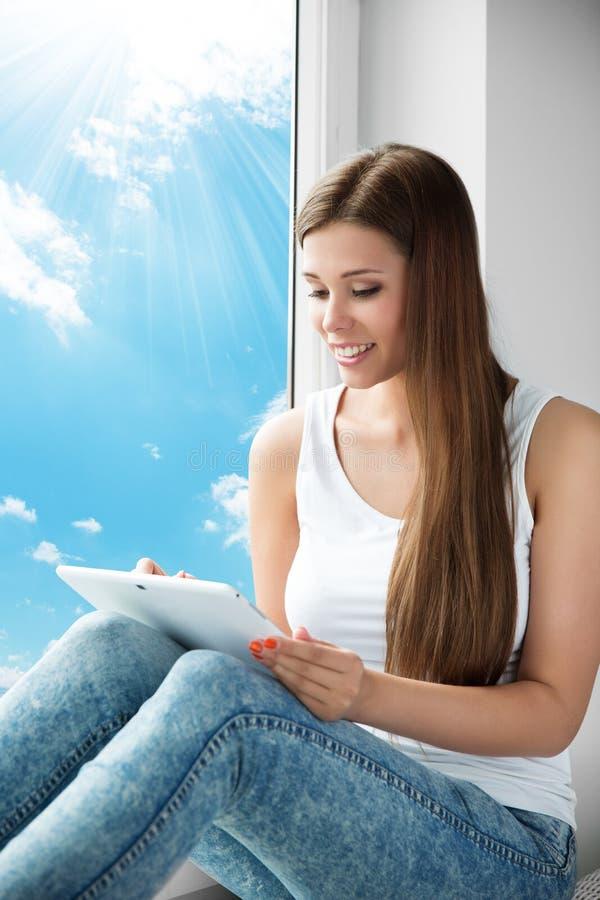 Frau, die Tablet-Fenster, junges Mädchen liest weiße Noten-Auflage verwendet lizenzfreies stockbild