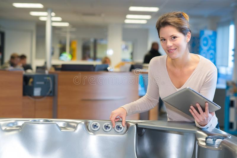 Frau, die Tablette im Möbelgeschäft überprüft stockfotografie